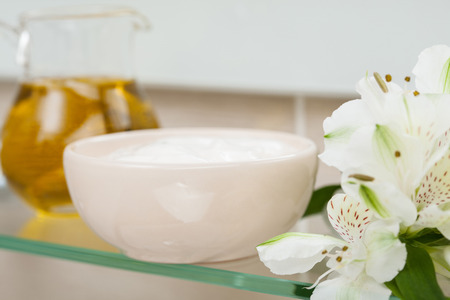 nourishing: Natural oil, nourishing mask and flowers on a bathroom shelf; spa and bodycare composition