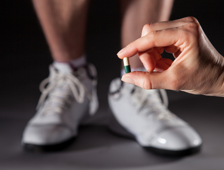 Hand holding capsule in front of sportsman's legs illustrating doping concept