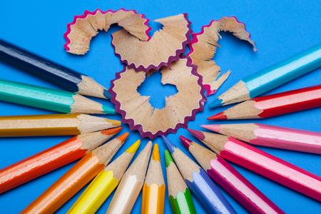 acuminate: Colorful pencils on blue background, closeup shot