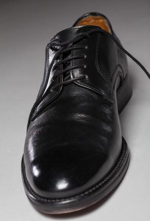 satined: Black leather male shoe, dark background