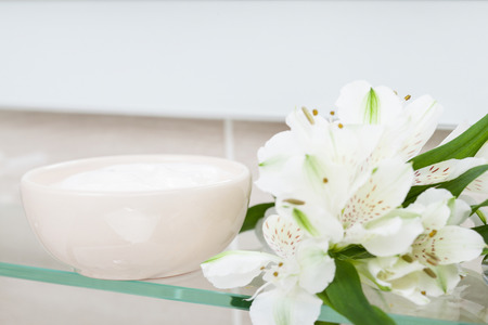 nourishing: Bowl with nourishing mask and beautiful fresh flowers on a bathroom shelf - spa and skincare concept