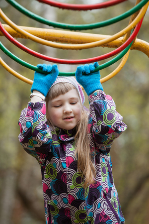 adroitness: Preschooler girl playing on the playground - closeup shot