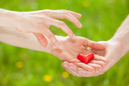 give out: Mans hand proposing a red heart to womans hand, light green background Stock Photo