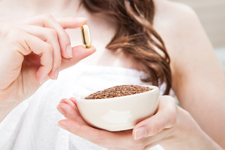 Woman hand holding bowl of flax seeds and Omega-3 capsule; beauty, skincare and haircare concept