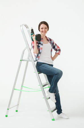 Happy young woman sitting on the stepladder and holding a screwdriver, white background