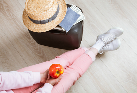 upper floor: Unrecognizable traveler with an apple waiting for a flight sitting near her belongings - upper viewpoint Stock Photo