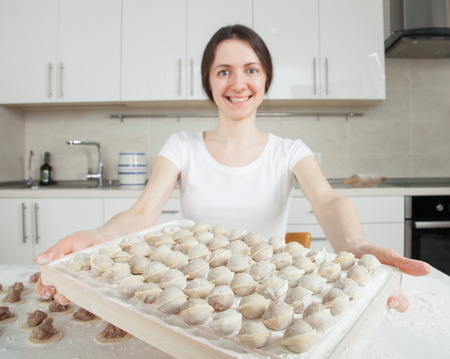 Housewife preparing meat dumplings - closeup shot photo