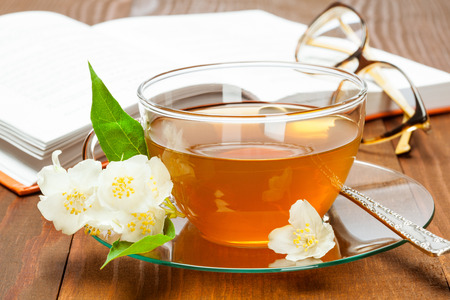 teatime: Teatime: a cup of jasmine tea, opened book and spectacles on wooden table Stock Photo