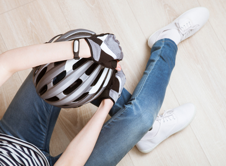upper floor: Relaxed sporty young woman sitting on the floor holding bicycle helmet - upper viewpoint