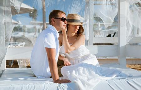 Happy young man and woman sitting under a beautiful white baldachin photo