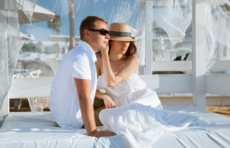 ble: Happy young man and woman sitting under a beautiful white baldachin