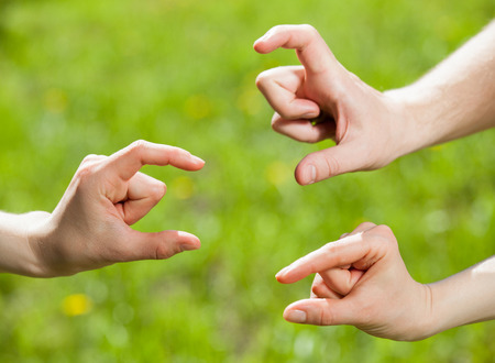 Hands showing different sizes - from small to big, natural green  background Stock Photo