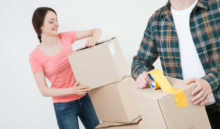 Young couple packing their things in cardboard boxes, neutral background photo