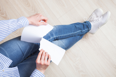 rend: Unrecognizable female hands tearing blank paper - upper viewpoint Stock Photo