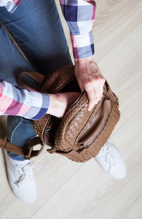 knapsack: Unrecognizable college student taking things for the lesson out of the knapsack, top view