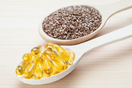 omega3: Sources of Omega-3: fish oil capsules and natural flax seeds for healthy hair, skin and nails Stock Photo