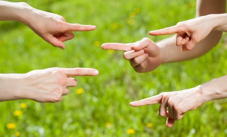 each: Hands pointing at each other on light green background Stock Photo