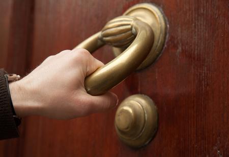 Human hand knocking old door, Italy