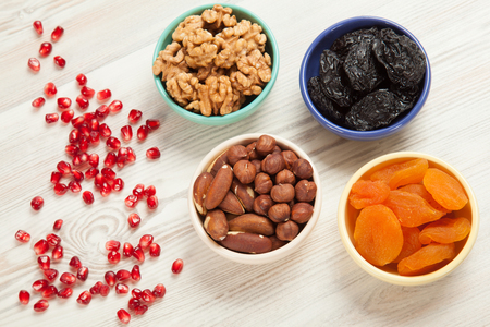 Bowls with dried fruits and nuts kernels on wooden table; variety of nuts and dried fruits for healthy snack; upper viewpoint