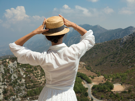 hilarion: Unrecognizable young woman in white dress looking at majestic mountain view touching her straw hat; territory of Saint Hilarion Castle, Northern Cyprus Stock Photo