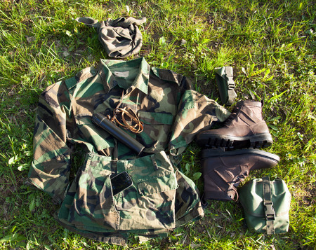 Military camouflage clothes and soldier belongings on the grass - top viewpoint