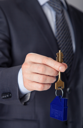 real estate sold: Unrecognizable businessman offering a key from a new house to you, closeup shot