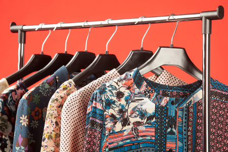 Trendy feminine clothes hang in a row on red background