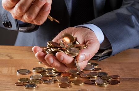 Businessmans hands holding many euro coins - closeup shot