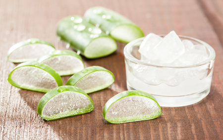 Fresh sliced aloe vera leaves and pulp on wooden table - concept of natural skincare