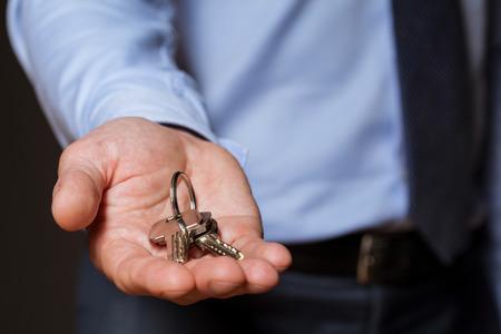 real estate sold: Unrecognizable businessman offering a keys, closeup shot