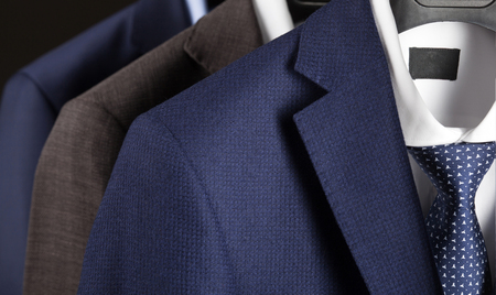 Elegant mans suits hanging in a row - closeup shot of classical mant suites