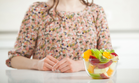 Healthy food for healthy lifestyle! Unrecognizable young woman having fresh fruit salad for breakfast Фото со стока