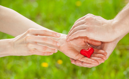 Mans hand proposing a red heart to womans hand, light green background Stock Photo