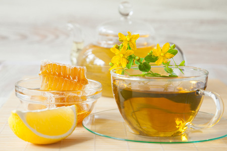 Beautiful composition of herbal tea served with honey and lemon on bamboo background