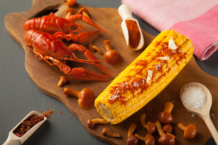 Boiled crayfish, sweet corns seasoned with ground cayenne pepper and marinated honey agarics on a wooden board