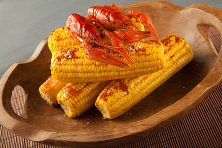 Boiled crayfish and sweet corns seasoned with ground cayenne pepper served in a wooden bowl