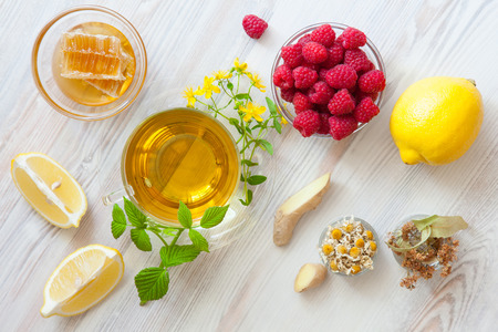 Composition of natural remedies for fast recovery: honey, fresh raspberries, herbal tea, lemon, ginger and dry herbs; upper viewpoint