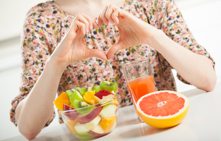 Unrecognizable young woman showing heart sign in front of the table with fresh fruit breakast illustrating her position towards healthy lifestyle Фото со стока