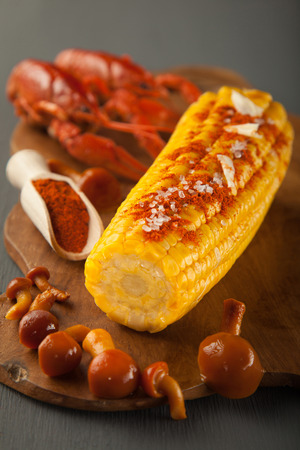 Boiled crayfish, sweet corns seasoned with ground cayenne pepper and marinated honey agarics served on a wooden board