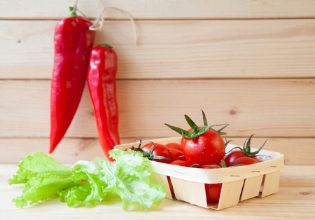 Composition of fresh raw vegetables: of red chili pepper, tomatoes and lettuce on wooden table Stock fotó