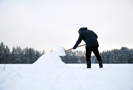 Man removing snow from a driveway after heavy snowfall in countryside