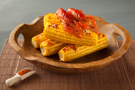 Boiled crayfish and sweet corns seasoned with ground cayenne pepper in a wooden bowl