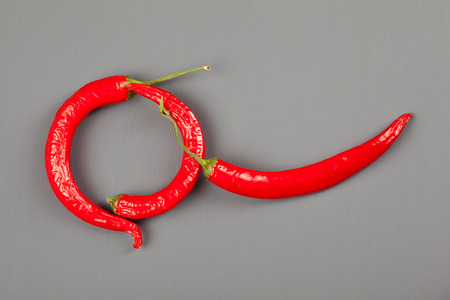 Group of red chili peppers on gray background Stock fotó