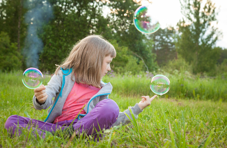 Funny preschooler girl making magic with soap bubbles sitting in a summer park Stock fotó