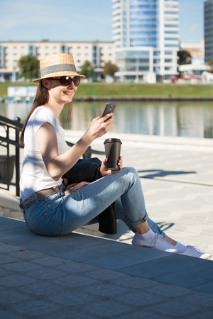 Happy young woman wearing casual clothes sitting on the staircase outdoors with a phone and a cup of coffee