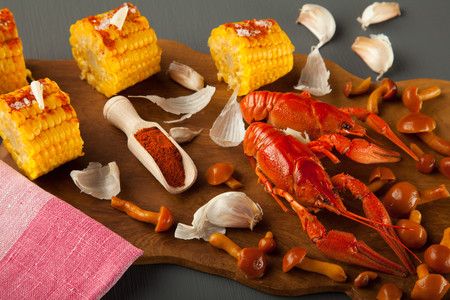 Boiled crayfish, sweet corns seasoned with butter and ground cayenne pepper, marinated honey agarics and spices on a wooden board
