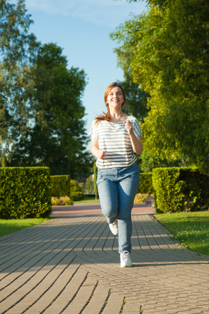 Happy young woman enjoying morning jogging in a summer park Stock fotó