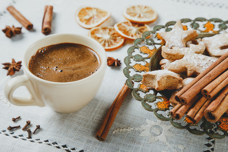 Cup of hot chocolate with cinnamon and homemade ginger cookies on linen tablecloth