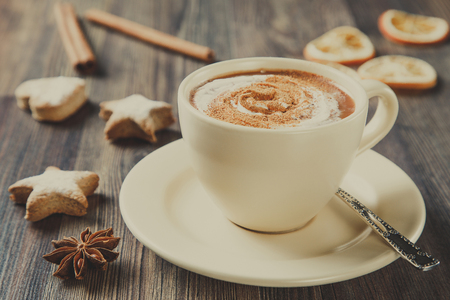 Cup of hot chocolate with cinnamon and homemade ginger cookies on wooden table