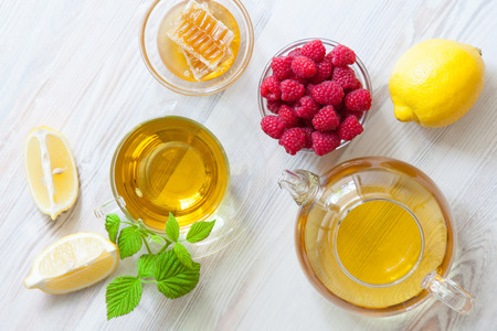 Composition of natural remedies for fast recovery: honey, fresh raspberreis, herbal tea and lemon; upper viewpoint